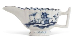 Lowestoft porcelain butter boat with scalloped rim and twig like handle, decorated in underglaze
