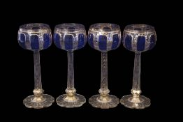 Group of four Bohemian style goblets, the bowls flashed in blue above faceted stems with a design in