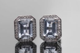 Pair of aquamarine and diamond earrings, the step aquamarines 7.09 x 4.96mm, raised within a small