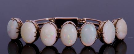 Articulated opal bracelet featuring seven graduated oval cabochon opals, each in cut down