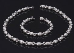 18ct white gold bracelet, a design of burnished oval beads and plain polished links, 18.5cm long,