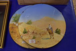 PAIR OF CIRCULAR GLASS STANDS WITH PRINTS OF MIDDLE EAST DESERT SCENES