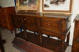 LOW DRESSER RAISED ABOVE A LOW SHELF ON TURNED LEGS TO A SHAPED FRIEZE BENEATH, THREE DEEP