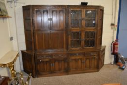 FOUR PART REPRODUCTION WALL UNIT WITH ROW OF CUPBOARDS SURMOUNTED BY GLAZED DISPLAY CABINET AND DROP