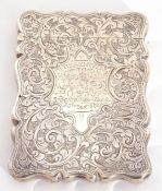 Late Victorian silver card case of shaped rectangular form, engraved all over with leaf sprays, with