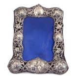 Late Victorian silver photograph frame with pierced and embossed border, decorated with cherubs,