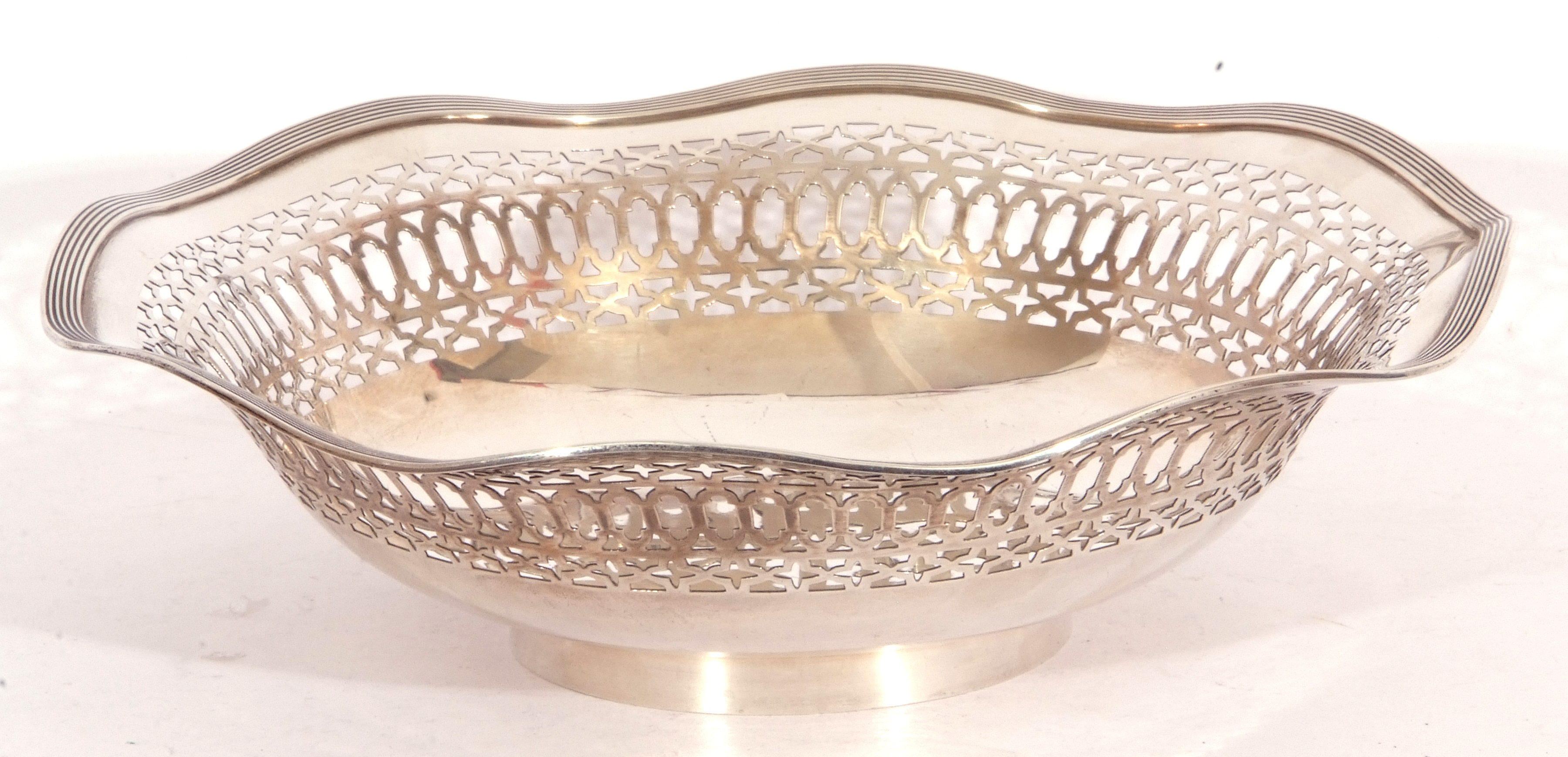 George V silver dish having pierced sides and reeded wavy rim and raised on a circular foot,