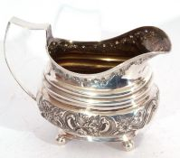 Georgian silver cream jug of oval form, ribbed with later embossed body, supported on four ball