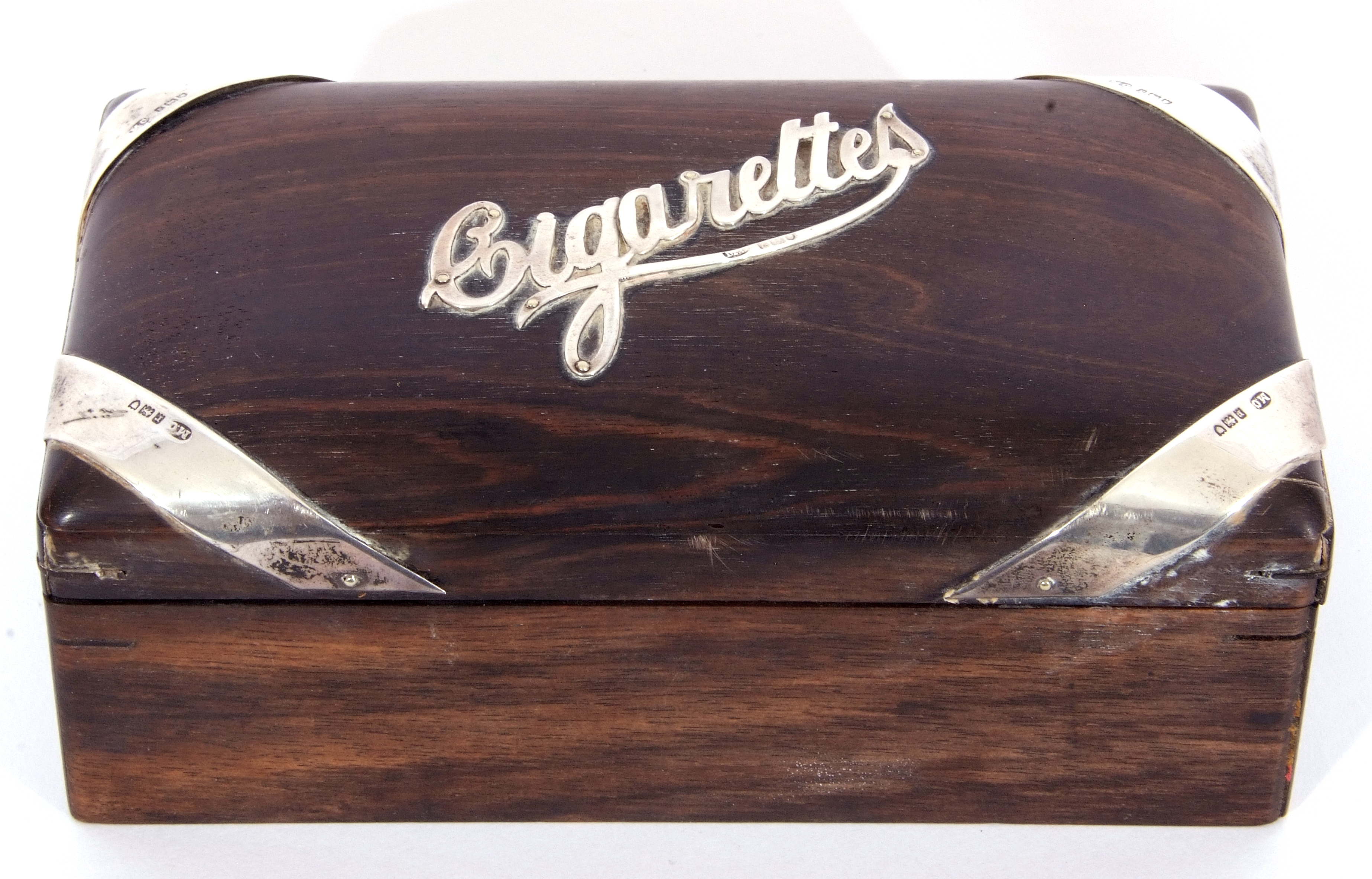 Hardwood and silver mounted table cigarette box of rectangular domed form, the centre applied with