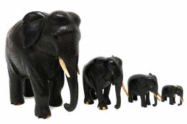 Group of four wooden models of elephants in graduated sizes