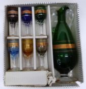 Boxed set of spirit glasses with a green glass jug with central gilt decoration to jug and