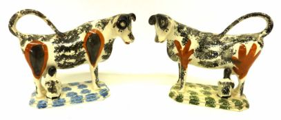 Pair of 19th century cow creamers with black sponged decoration with ochre patches, on sponged