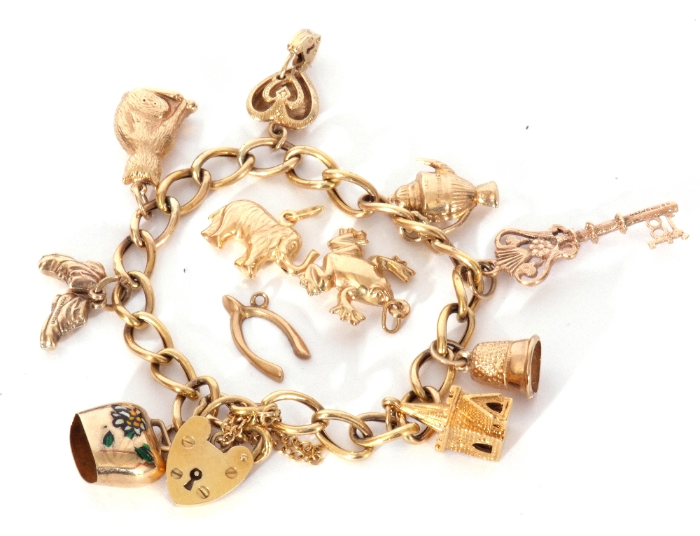 9ct gold curb link bracelet suspending various charms to include a key, cat, church etc (three loose