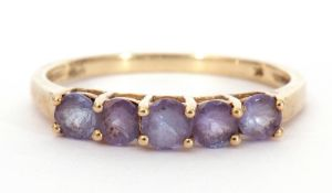 Modern 9K stamped ring set with five purple coloured stones, size O