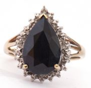 Modern haematite and diamond ring, the pear shaped centre faceted stone raised above a small diamond