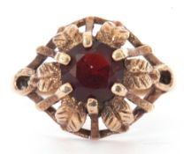 9ct gold and garnet ring centring a round faceted garnet, claw set in a pierced and engraved leaf