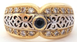 Two-tone yellow metal filigree fronted design ring, centring a small sapphire and highlighted with