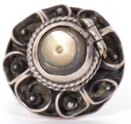 White metal filigree poison ring, the hinged mother of pearl lid opening to a vacant reservoir,