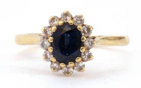 18ct gold sapphire and diamond cluster ring, the oval shaped faceted sapphire 6 x 4mm, within a