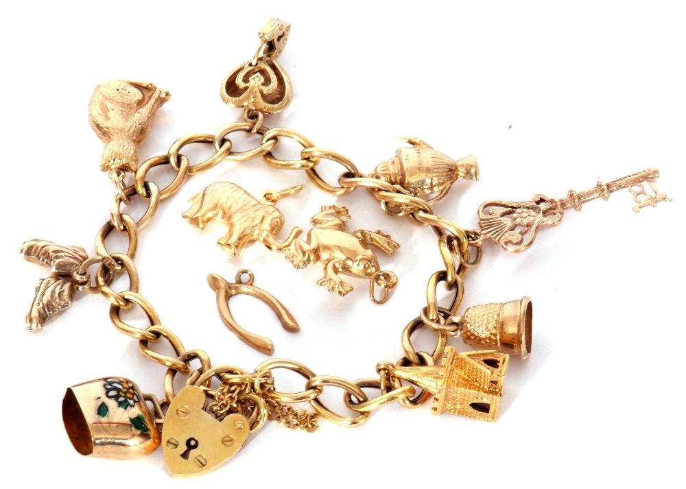 9ct gold curb link bracelet suspending various charms to include a key, cat, church etc (three loose - Image 2 of 3