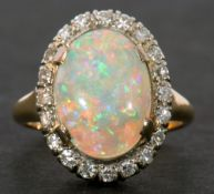 Opal and diamond cluster ring, the oval shaped cabochon opal 14 x 10mm approx, surrounded by 20