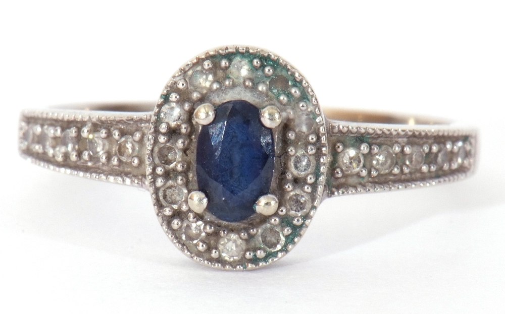 Modern 375 stamped synthetic sapphire and diamond ring, the oval shaped centre stone raised above
