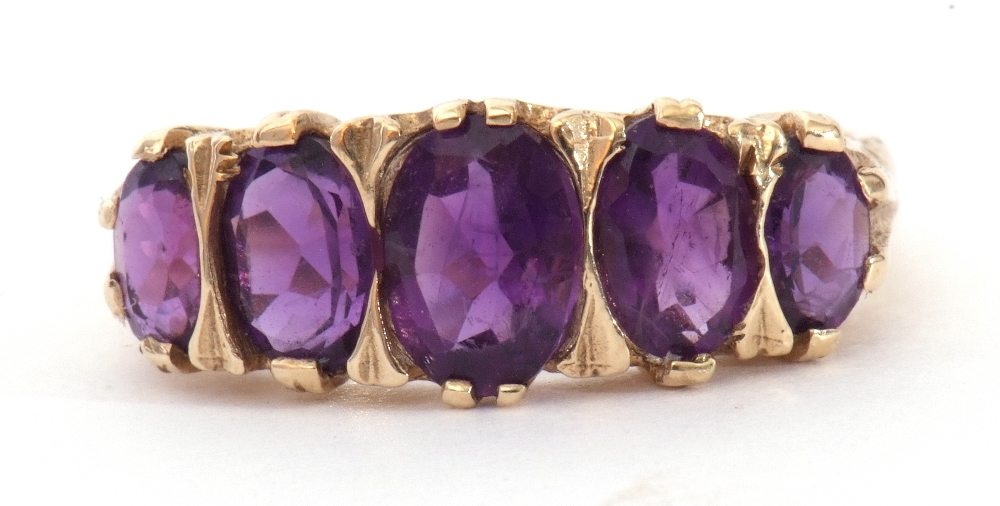 9ct gold amethyst five stone ring, featuring five graduated oval shaped amethysts, all in a carved
