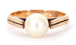 9ct stamped and cultured pearl ring, a single full pearl raised between upswept shoulders to an
