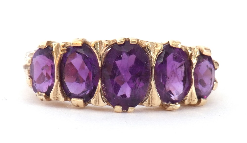9ct gold amethyst five stone ring, featuring five graduated oval shaped amethysts, all in a carved - Image 2 of 9