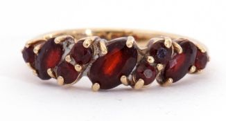 9ct gold garnet ring, alternate set with oval and round shaped small garnets, each individually claw