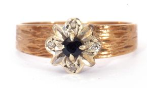 9ct gold sapphire and diamond ring centring a round cut sapphire, raised above four small diamond
