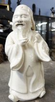 Unusual white pottery glazed figure of a Chinese deity, 15cm high