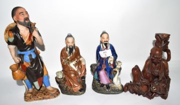 Group of four Oriental figures, one carved wooden figure with a tiger and three other figures of
