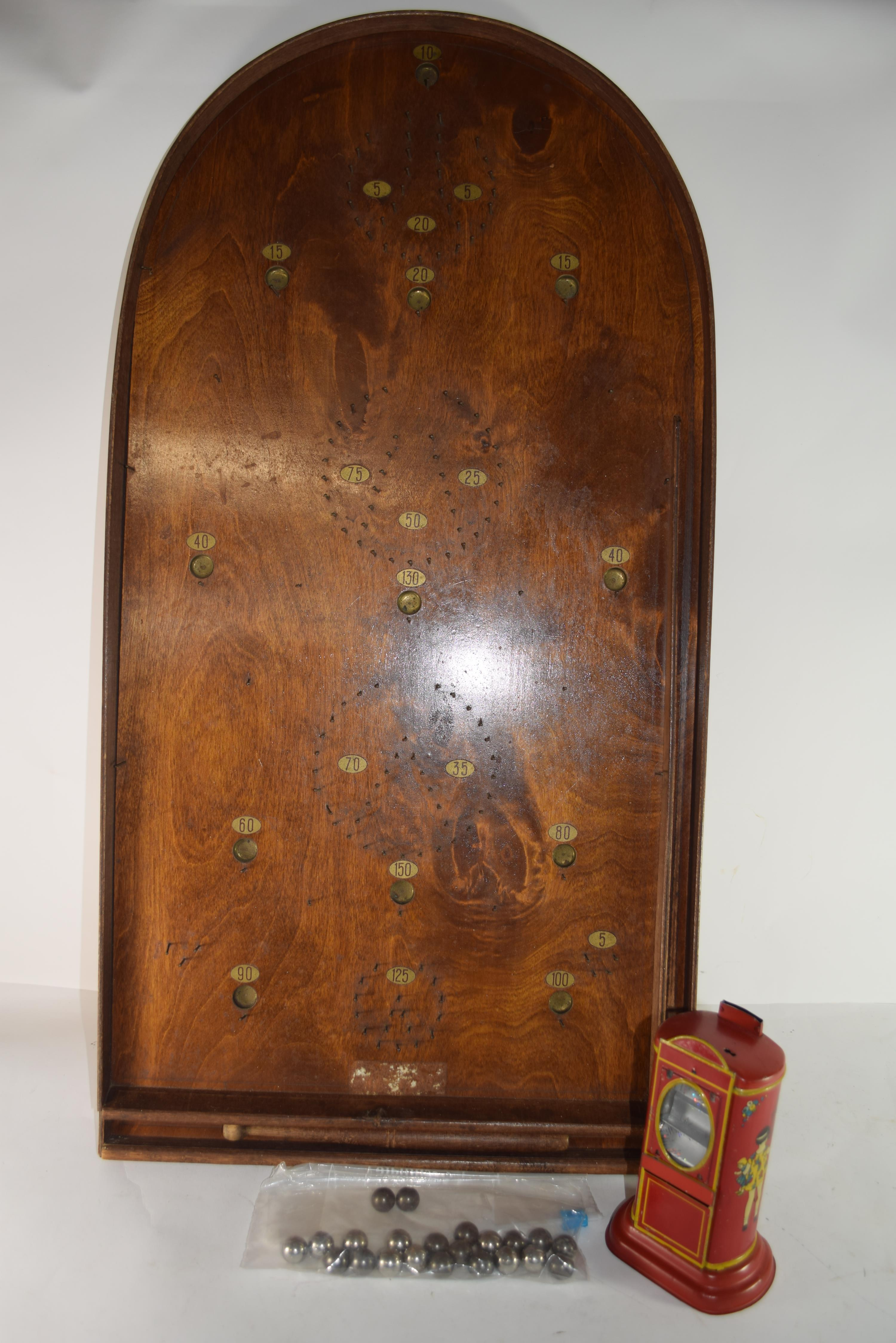 Wooden bagatelle game with silver balls, together with a 1930s child's money box