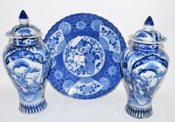 Two Japanese porcelain blue and white vases and covers, Meiji period, decorated with panels of