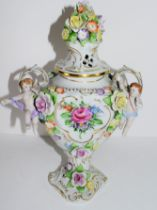 Continental porcelain vase and cover with floral design, the knop with applied flowers, loop handles