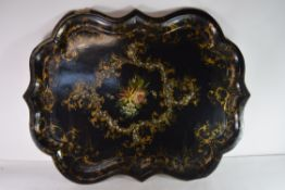 Large shaped papier mache tray with central decoration of flowers within scrolling gilt borders,