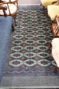 Green and Brown patterned wool carpet, decorated with medallions and a gulled border, 9ft x 5ft8