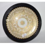 Wall plate with a gilt design encased in a wooden and glazed mount, 28cm diam