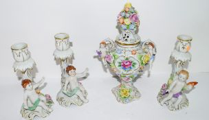 Small Continental porcelain vase floral decoration with handles flanked by cherubs, the cover with