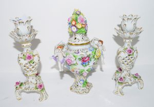 Pair of Continental porcelain candlesticks and a small vase with cover with applied flowers, the