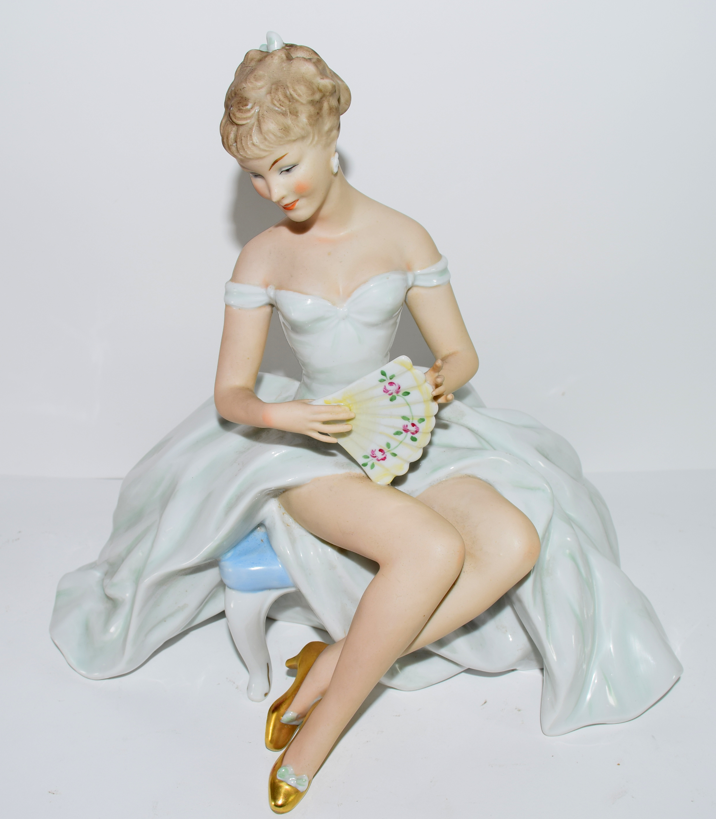 Continental porcelain figure of a young girl seated on a bench with fan, 27cm high