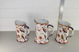 GRADUATED SET OF THREE HAND DECORATED WATER JUGS, LARGEST APPROX 22CM