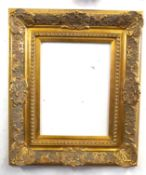 A gilt picture frame in decorated shell and foliate. Approx 27x21in inches.