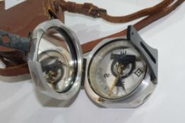 E R Watts, London, metal cased bearing compass in fitted leather case, compass approx 7.5cm wide