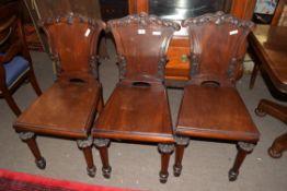 Set of three Georgian mahogany hard seated hall chairs, the backs with foliate carved decoration