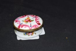 Small 19th century oval enamel pill or patch box decorated with painted floral detail, 5cm wide