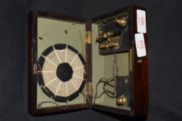 Primitive crystal radio set in a simulated rosewood case of hinged rectangular form, 18cm wide, no