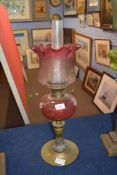 Late Victorian oil lamp with frilled cranberry tinted shade with floral decoration, clear glass