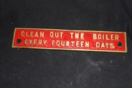 """Small cast brass plaque marked """"Clean out the boiler every 14 days"""", 25cm wide"""
